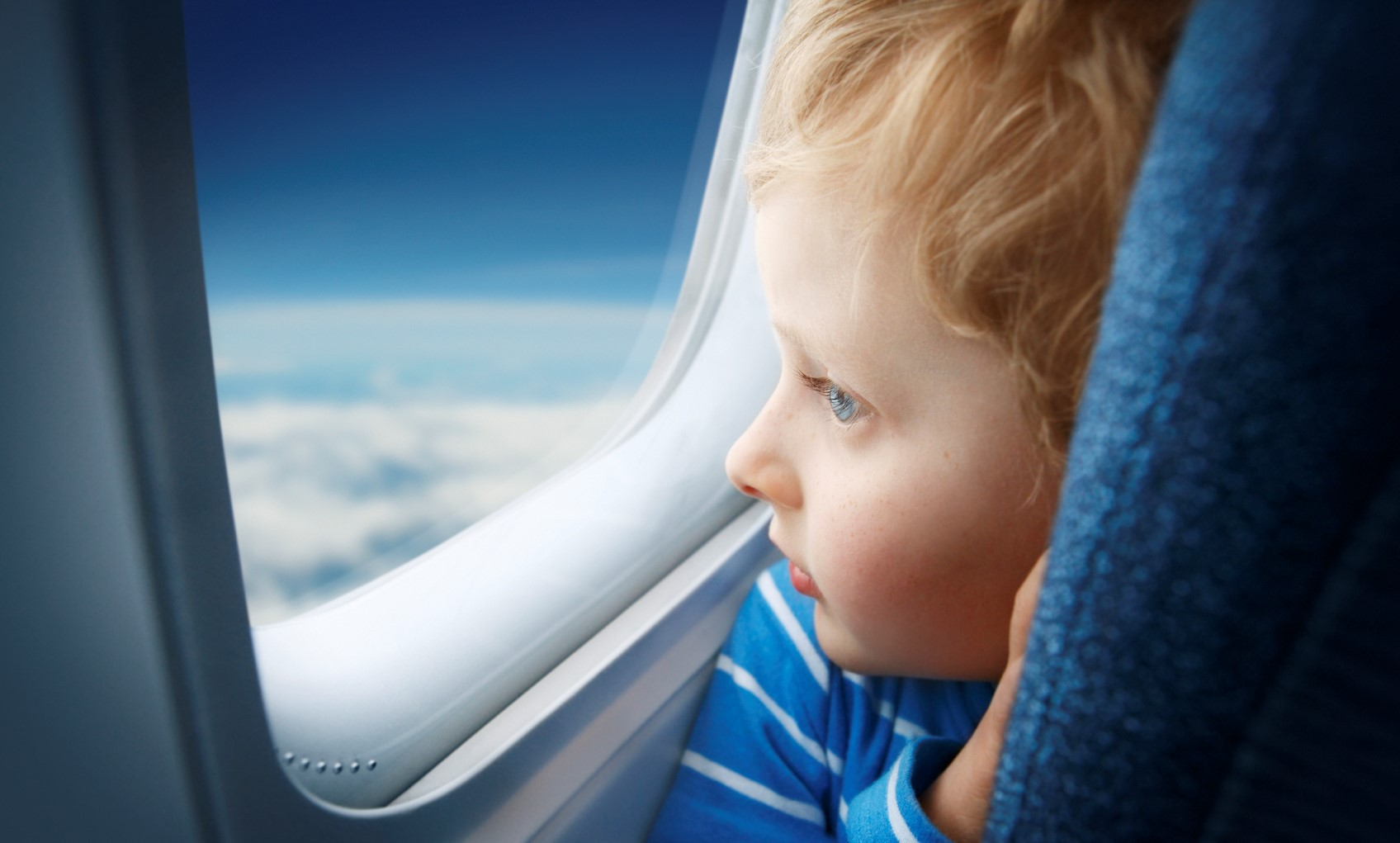 Boy watching sky through the airplane window